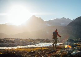Hiker looking at the mountains during sunset near river, Near Camp In Tasiilaq Fjord. By Chris Brinlee Jr