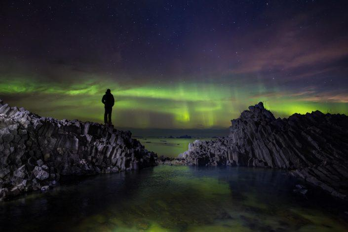 Hiker standing on volcanic rooks on Disko Island in North Greenland looking at northern lights dancing over the ocean. By Paul Zizka