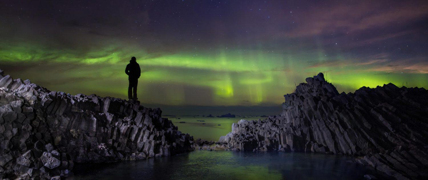 Hiker standing on volcanic rooks on Disko Island in North Greenland looking at northern lights dancing over the ocean. Photo by Paul Zizka