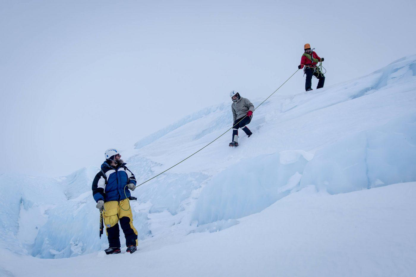 Hikers on the Greenland ice sheet using ropes to descned an ice wall near Ilulissat. By Mads Pihl