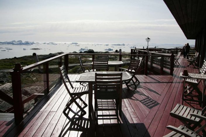 Outdoor terrace of Brasserie Ulo with a view to Ilulisast Icefiord in North Greenland. Photo by Hotel Arctic