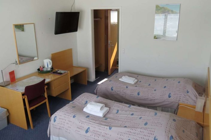 Bedroom with two single beds, large TV and study area. Photo by Hotel Kap Farvel, Visit Greenland