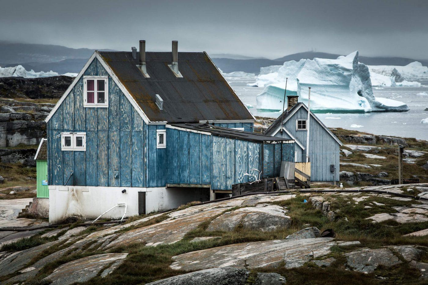 Houses with icebergs in the background in Oqaatsut, Greenland. By Mads Pihl