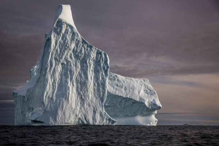 Icebergs - A huge iceberg and a tiny boat near Tasiilaq in East Greenland