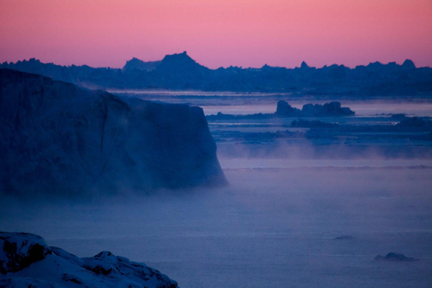 Icebergs shrouded in ice mist near the Ilulissat Ice Fjord in Greenland, by David Trood