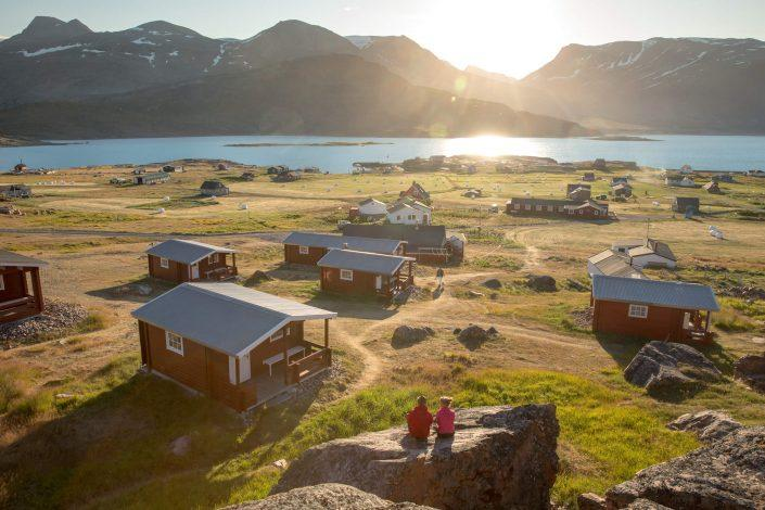 Two guests enjoying the sunset at the Blue Ice hut accommodation in Igaliku in South Greenland