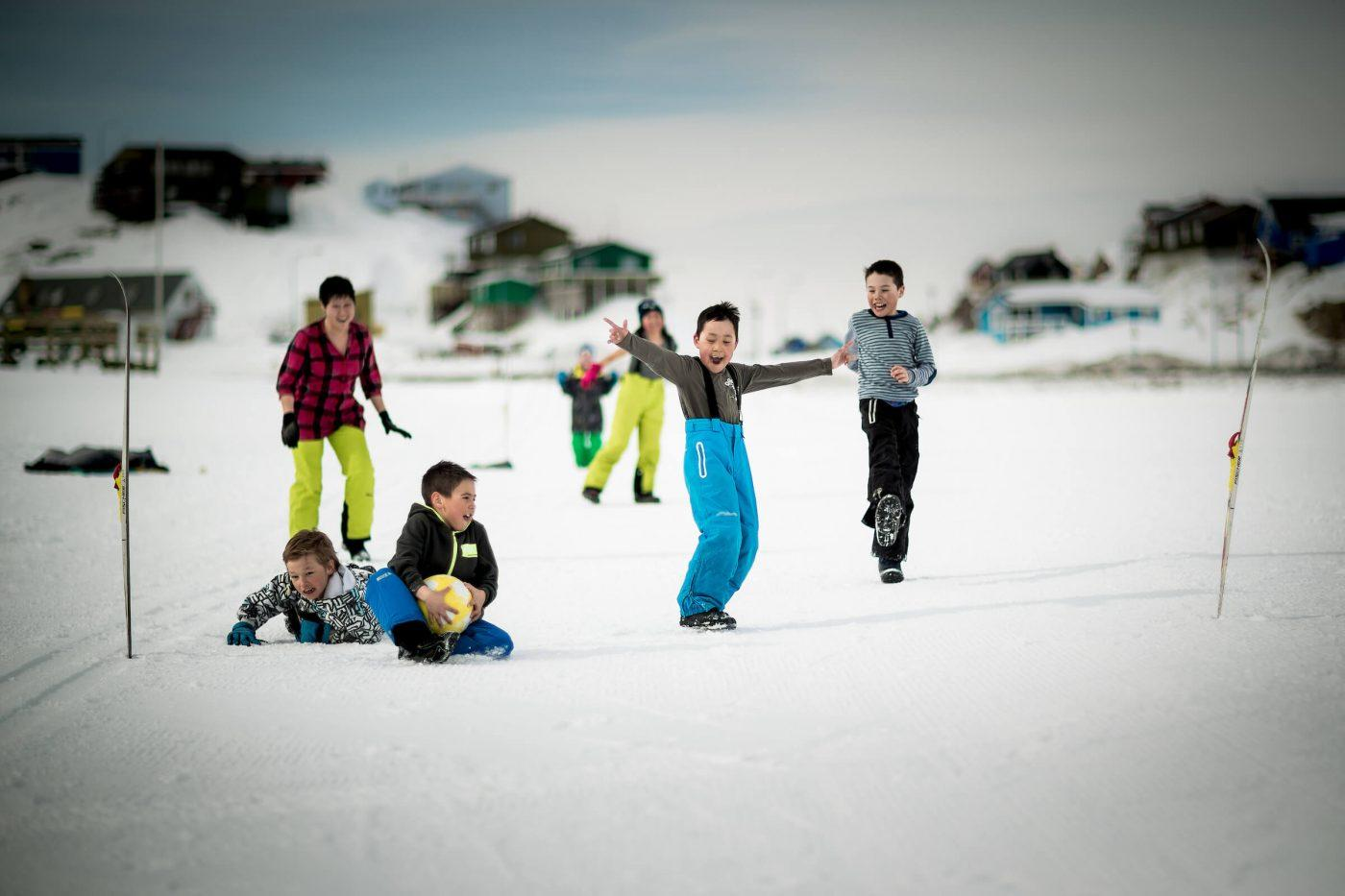 Kids playing soccer on the lake ice in the center of Sisimiut in Greenland. Photo by Mads Pihl - Visit Greenland