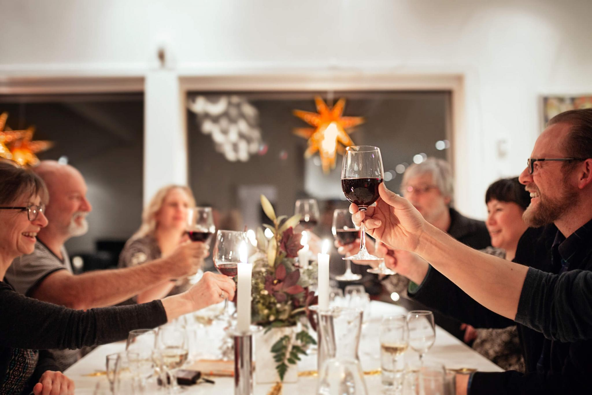 Locals and tourists sharing a toast during a christmas dinner in the Margrethe Suite in Nuuk in Greenland. Photo by Rebecca Gustafsson