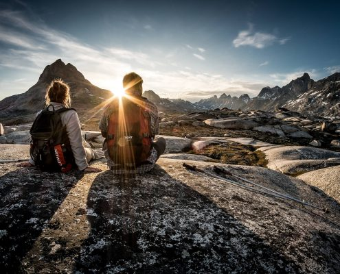 Midnight Sun - Two hikers enjoying the sunset near Qenertivartivit in Ammassalik Fjord near Kulusuk in East Greenland