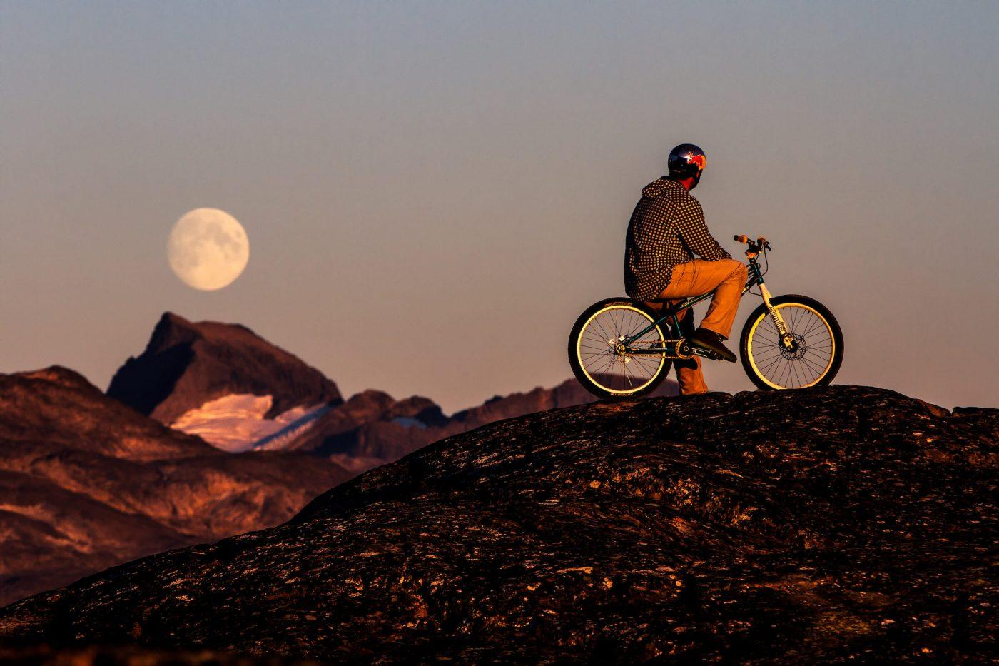 Red Bull trial biker Petr Kraus and the full moon at sunset in Kangaamiut in Greenland. By Mads Pihl