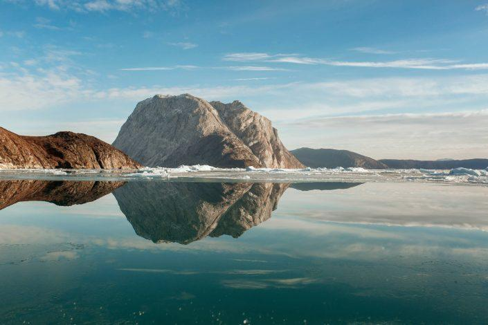 Mountains being reflected perfectly on clear water in the Nuuk fjord in Greenland