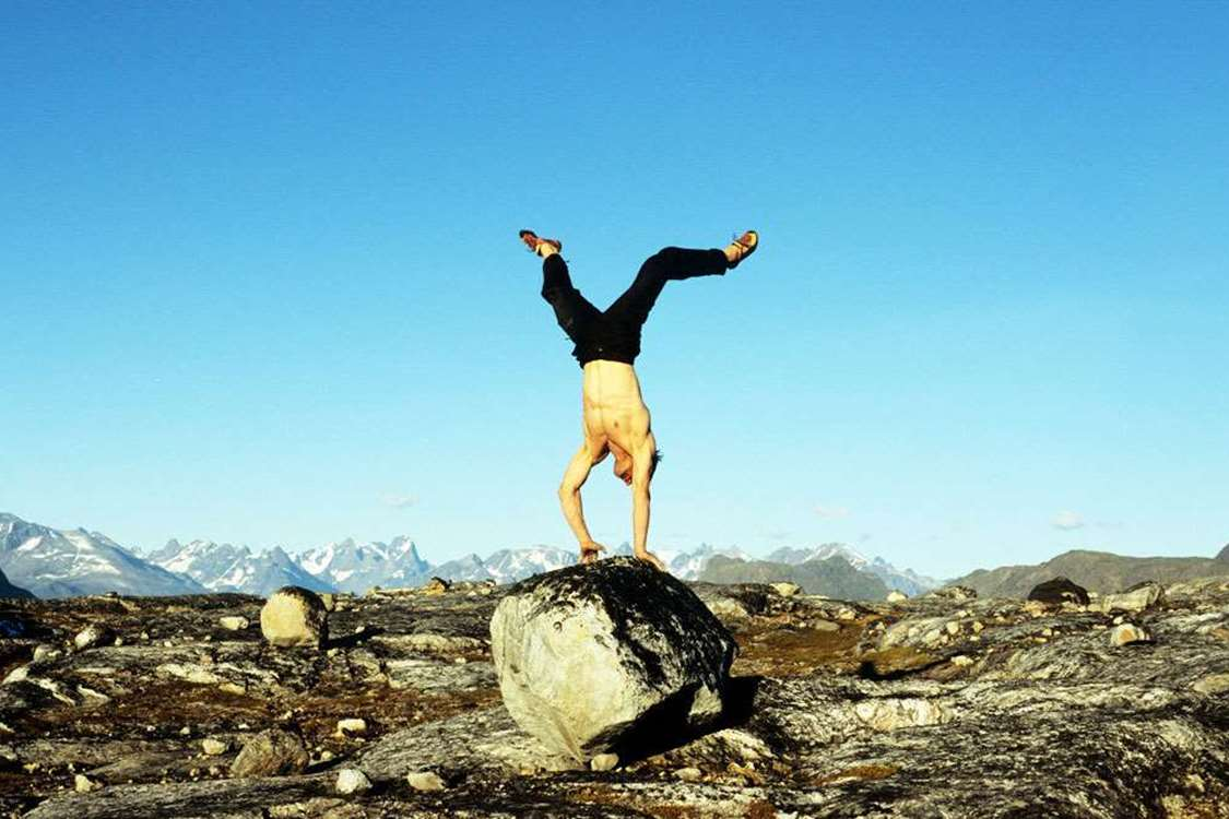 Shirtless man doing a handstand on a rock in South Greenland. Photo by Nanortalik Tourism Service