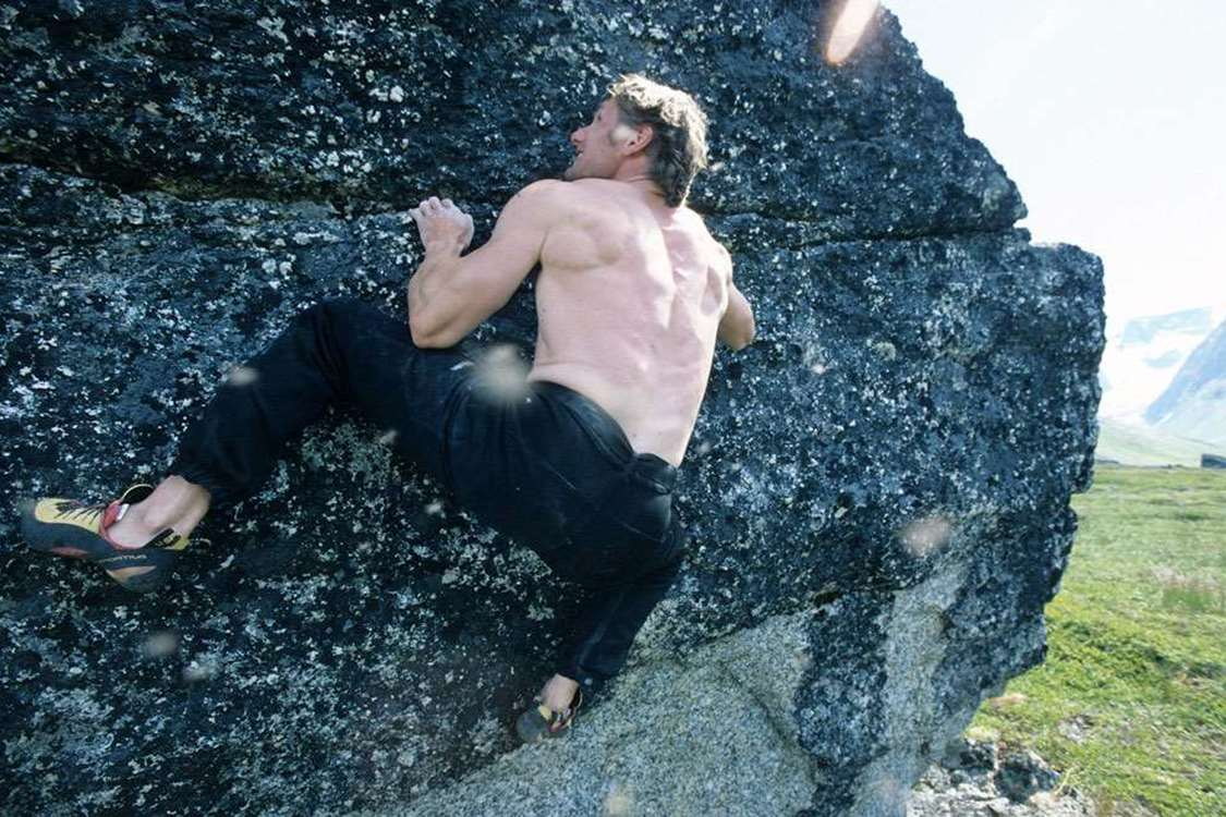 South Greenland rock climbing with a shirtless man climbing in Summer. Photo by Nanortalik Tourism Service