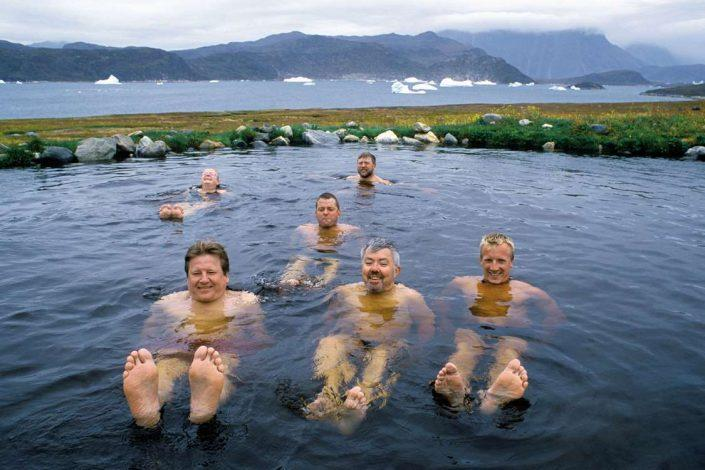 Tourists enjoying the hot springs of South Greenland with icebergs in background. Photo by Nanortalik Tourism Service