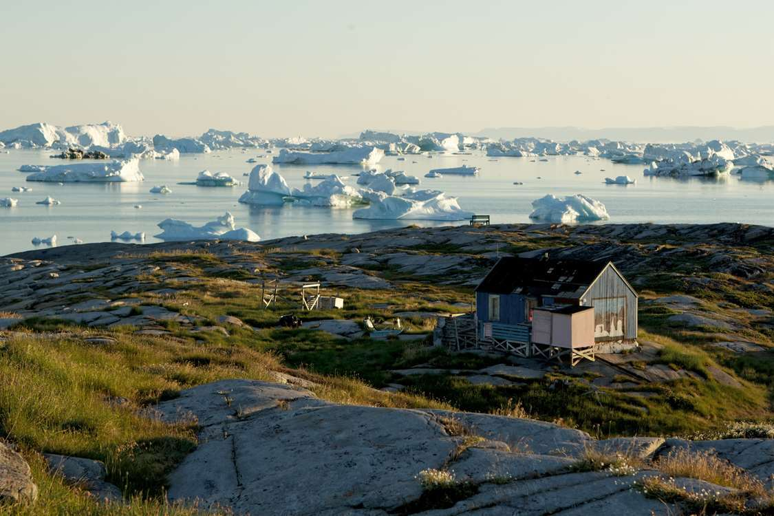 A blue house with icebergs in background in Oqaatsut in the Disko Bay, Greenland. Photo by North Greenland Adventure