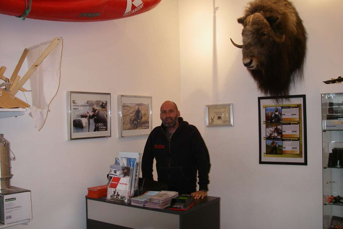 CEO Thomas Nielsen at the cash register of North Safari Outfitters with musk ox head hanging on wall. Photo by North Safari Outfitters
