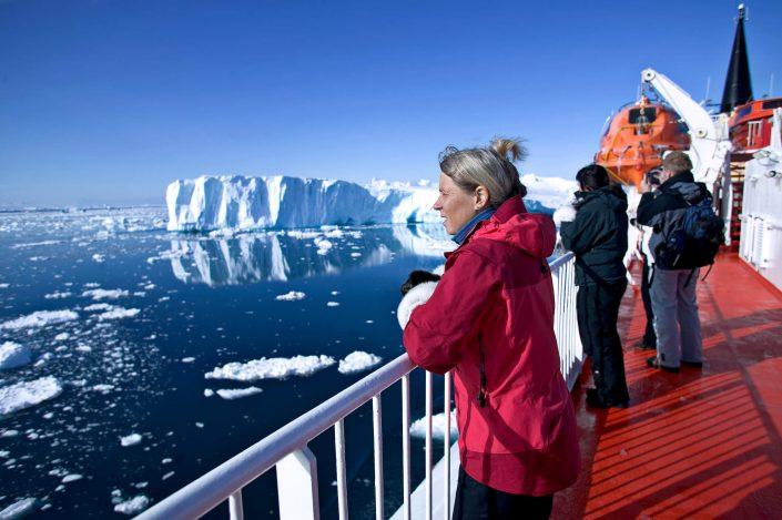 Passengers standing on the deck of coastal ferry Sarfaq Ittuk in a sunny weather in Greenland
