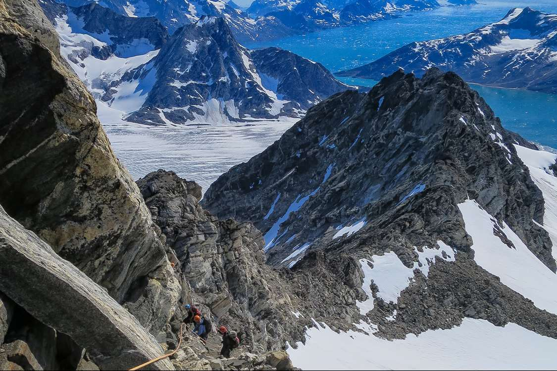 Climbers climbing a steep mountain in East Greenland in Summer. Photo by Pirhuk - Greenland Expedition Specialists