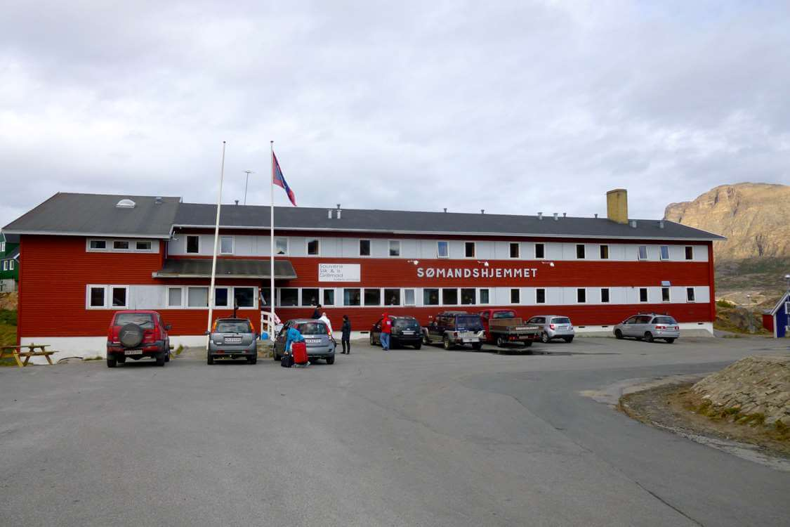 Frontal view of The Sisimiut Seamen's Home and parking area. Photo by Hotel Sømandshjemmet, Visit Greenland