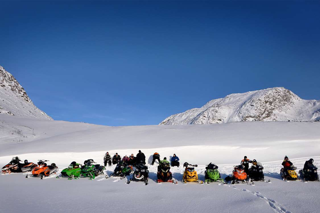 A group of snowmobilers taking a break in the snow near Sisimiut. Photo by Mads Pihl, Visit Greenland