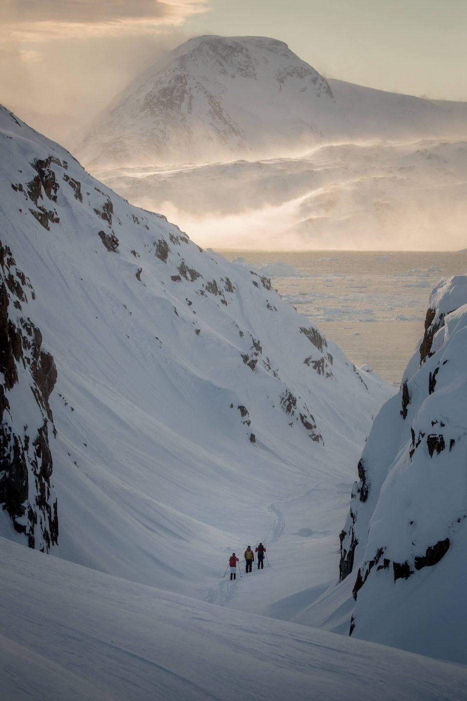 Skiers in a narrow valley near Sermilik Ice Fjord in East Greenland