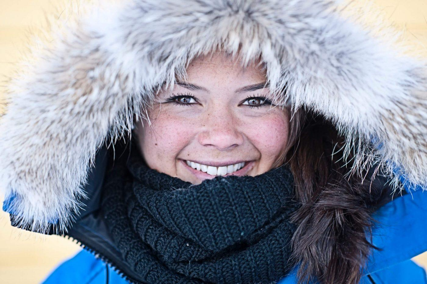 Smiling young greenlandic woman in winter, by Andre Schoenherr