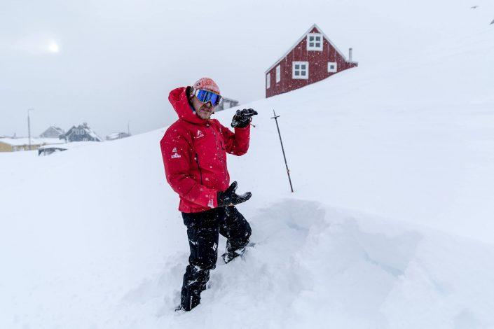 The ski touring guide measuring fresh snow depth in Kuummiut in East Greenland. Photo by Mads Pihl