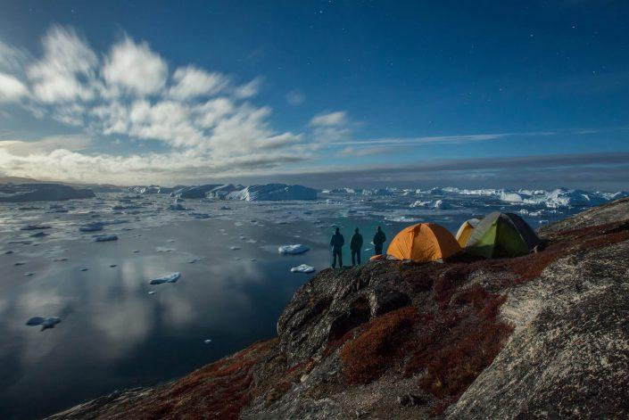 Three campers standing outside their tents overlooking the Ilulissat icefjord in North Greenland on an autumn day. By Paul Zizka