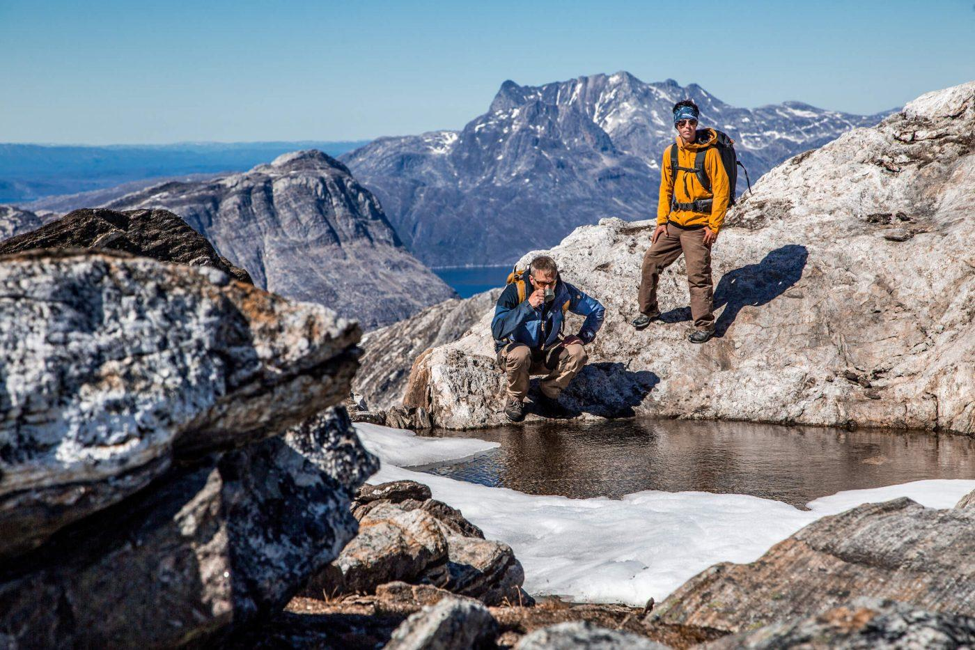 Touring Greenland guide stops for a drink of fresh water from a meltwater pond at the top of Kingittorsuaq mountain outside of Nuuk with a view straight to Sermitsiaq mountain. Raven Eye Photography