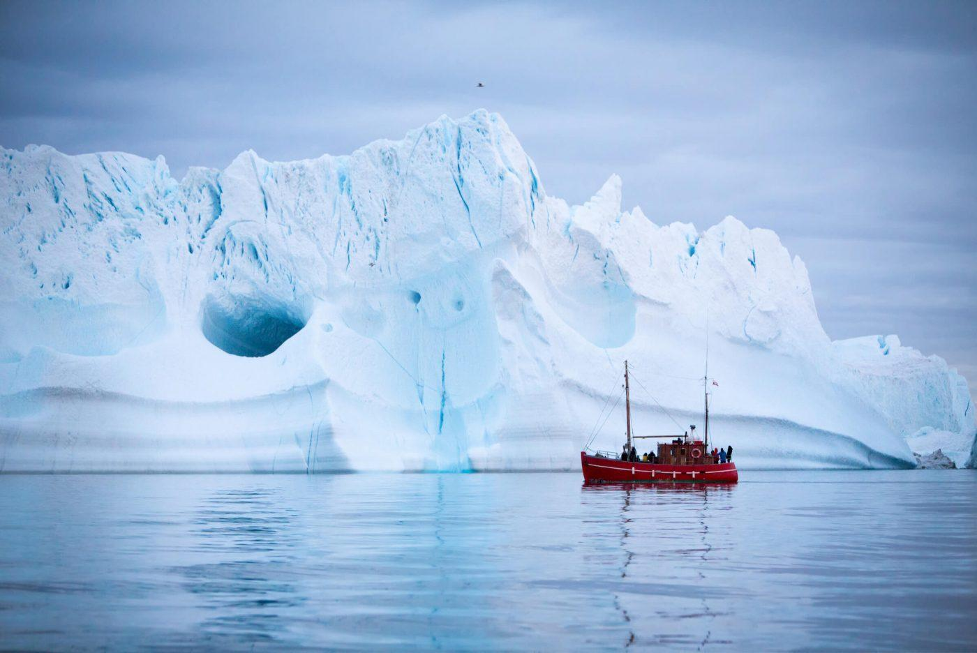 Tourists on a boat tour sailing by a giant iceberg near Ilulissat in North Greenland. By Paul Zizka