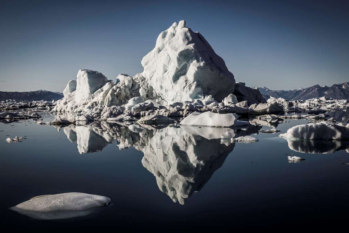 Large iceberg mirrored in clear water. Photo by Arctic Dream, Visit Greenland