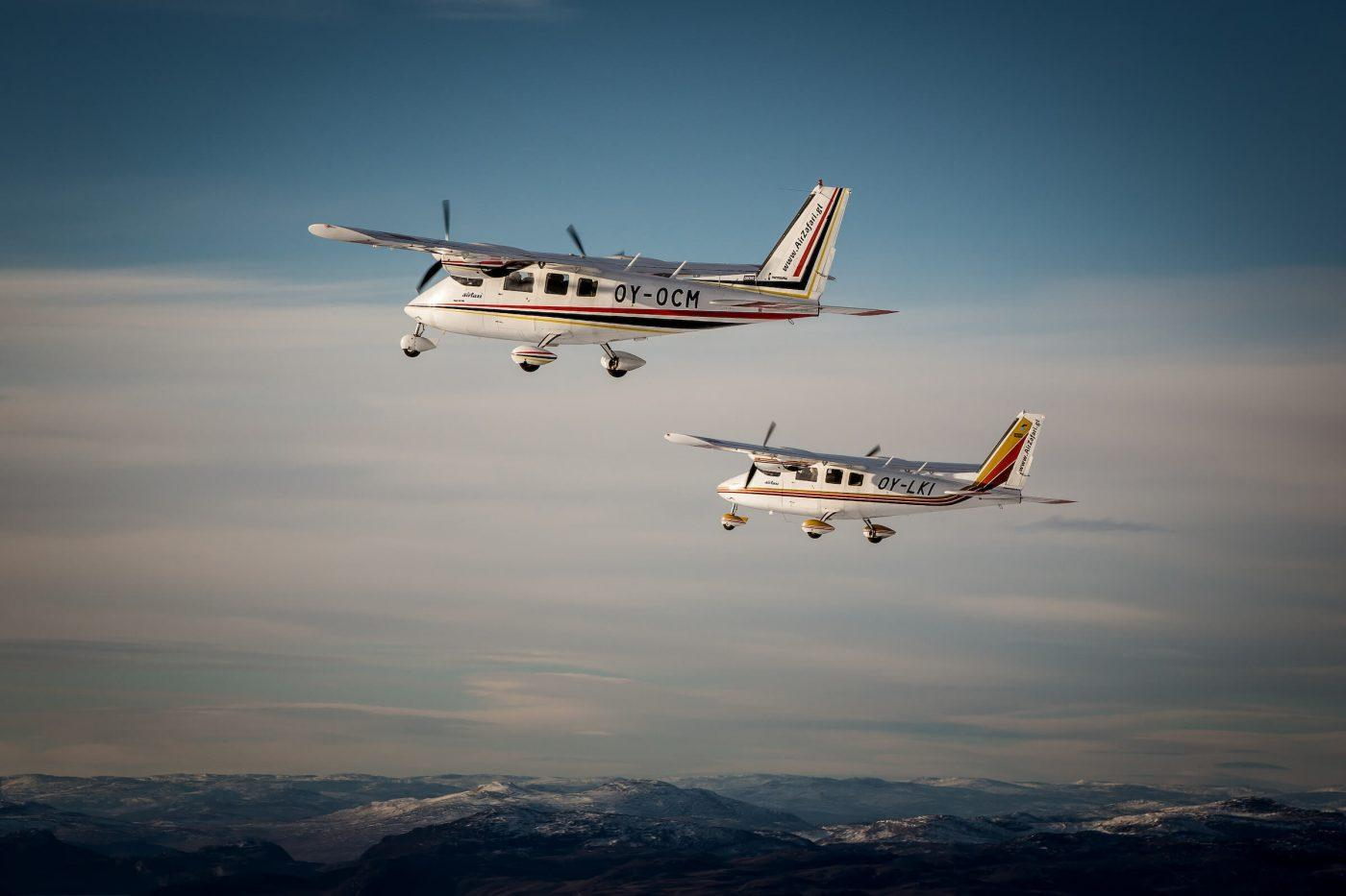 Two flightseeing planes from Air Zafari over the hills around Kangerlussuaq in Greenland. Photo by Mads Pihl
