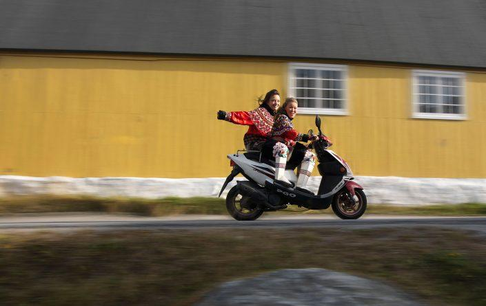 Two greenlandic women in national costumes on a scooter, by David Trood
