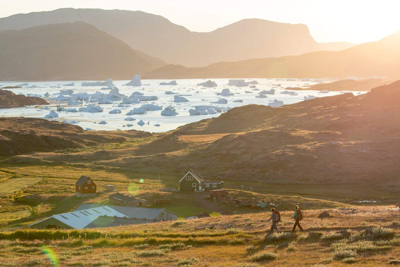 Two hikers approaching Tasiusaq sheep farm in South Greenland. By Mads Pihl