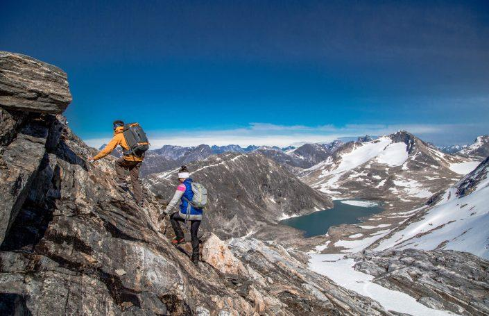 Two hikers nearing the summit of Kingittorsuaq mountain outside of Nuuk, the capital of Greenland. By Raven Eye Photography