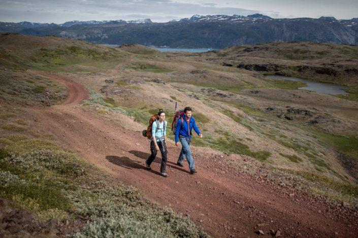 Two hikers on the red dirt roads between Qassiarsuk and Tasiusaq sheep farm in South Greenland. By Mads Pihl