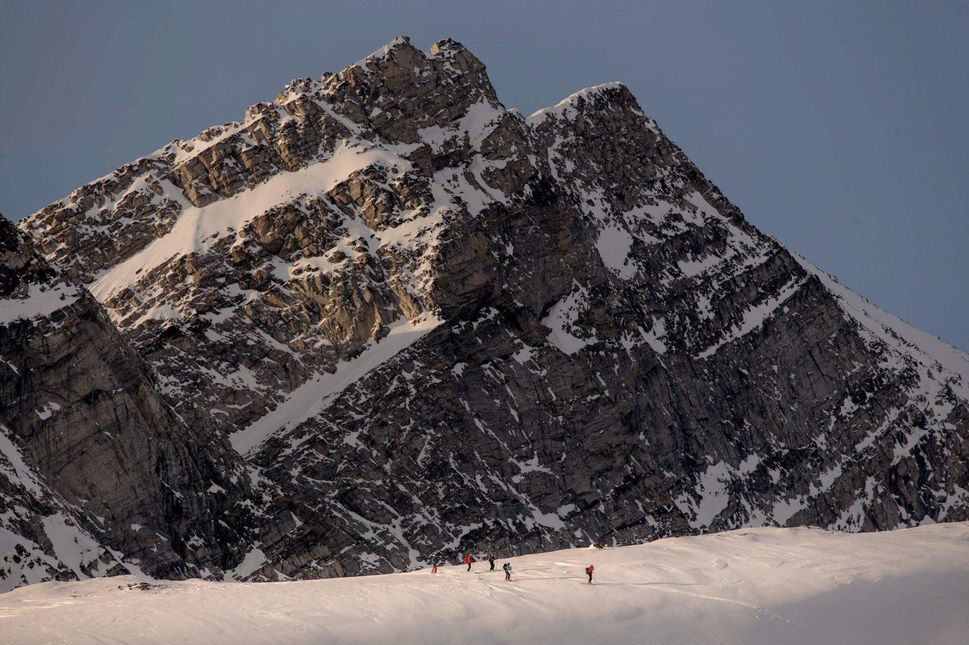 Skiers beneath mountain near Kuummiit. By Mads Pihl