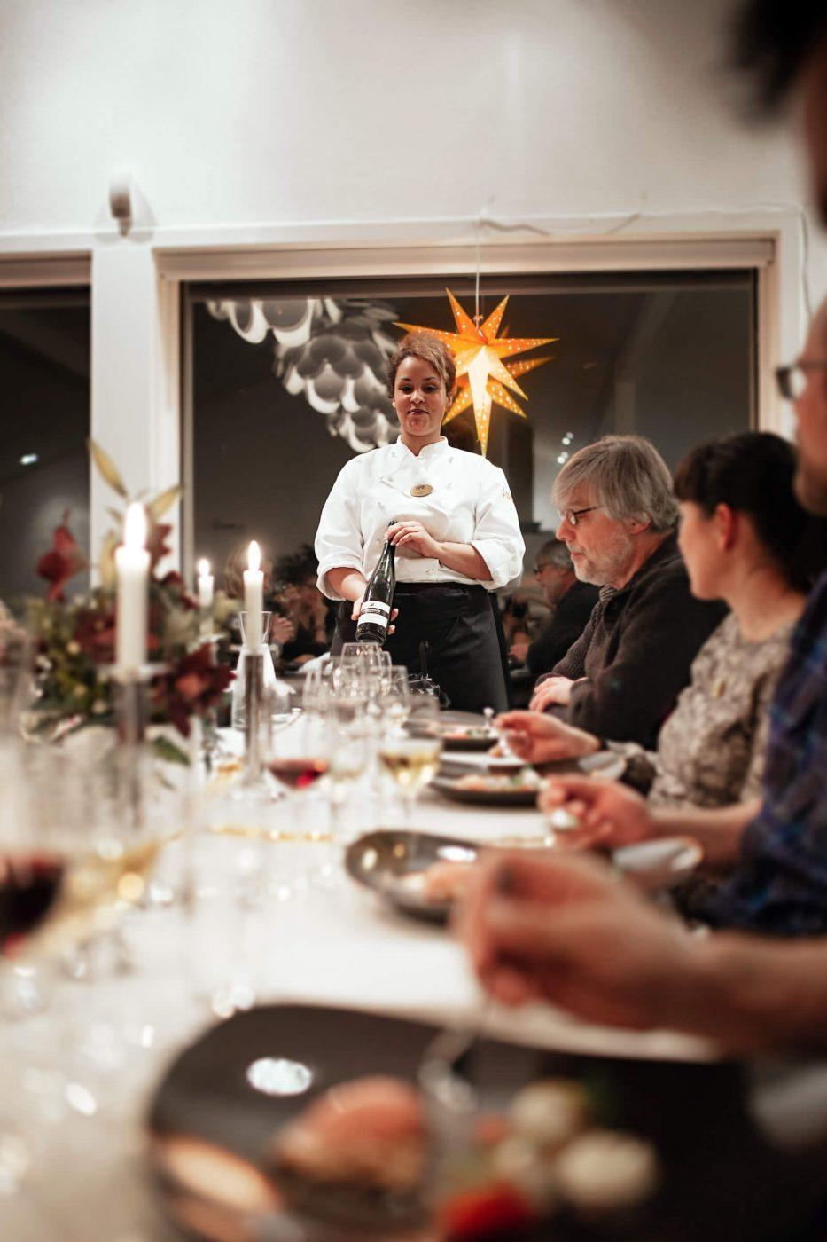 Waiter from Hotel Hans Egede presenting wine to locals and tourists having a christmas dinner at the Margrethe Suite in Nuuk in Greenland. By Rebecca Gustafsson