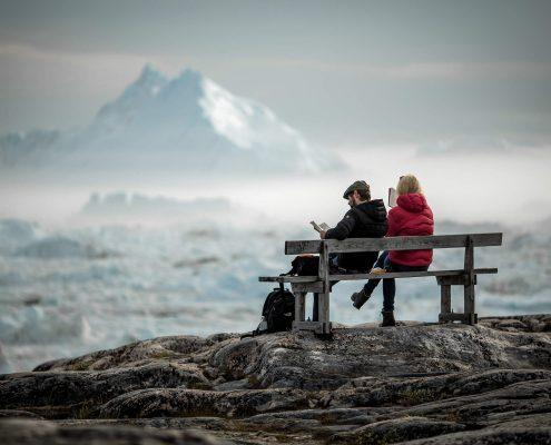 Two travelers reading on a bench overlooking icebergs in the Ilulissat ice fjord in Greenland. Photo by Mads Pihl