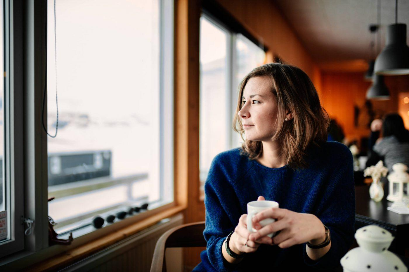 Woman having coffee and enjoying the view in Inuk Hostels in Nuuk in Greenland. By Rebecca Gustafsson - Visit Greenland